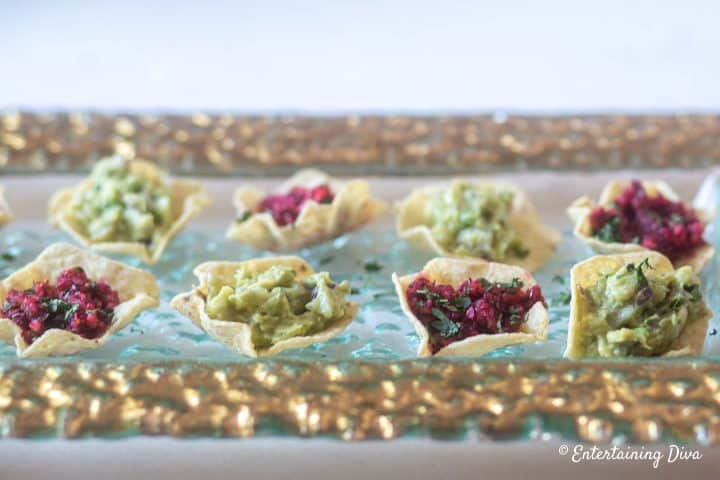 Avocado guacamole dip with tortilla chips and cranberry salsa bites