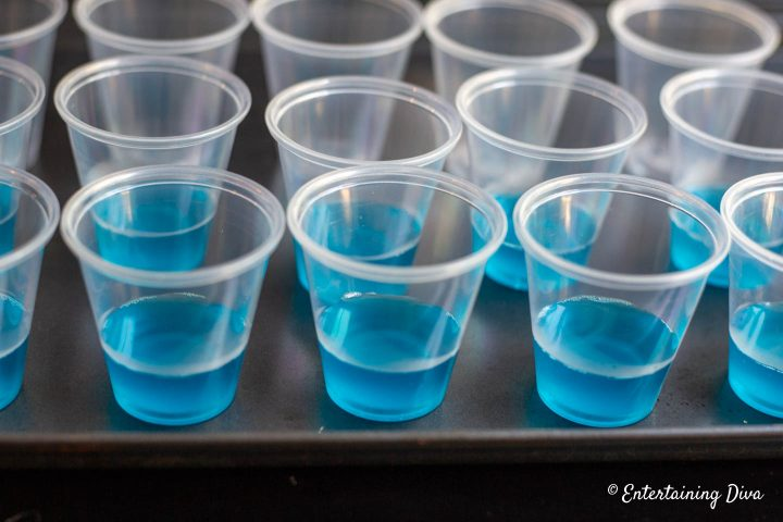 Jello shot cups filled part way with blue jello