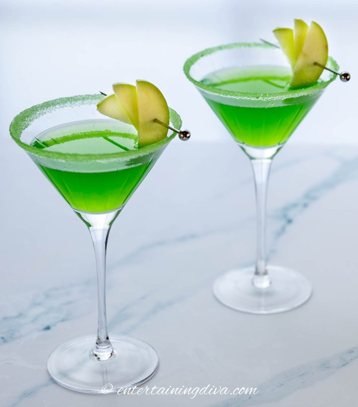 Appletini mocktail garnished with 3 granny smith apple wedges on a cocktail pick