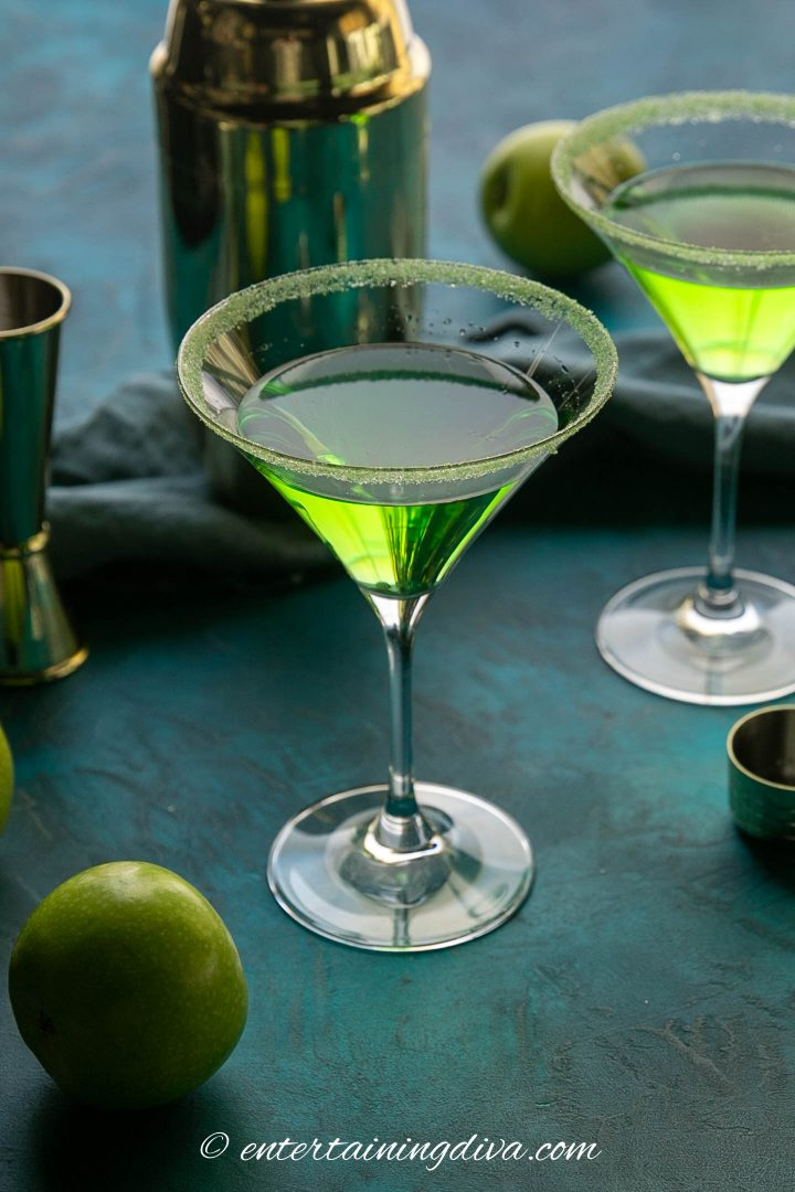 apple martini on a blue green background with a cocktail shaker