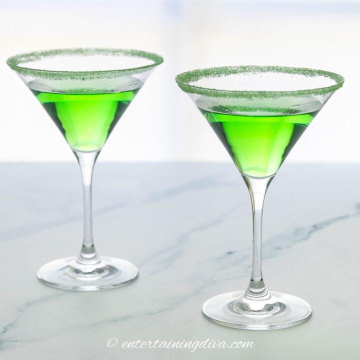 sour apple martini in martini glasses rimmed with green sugar