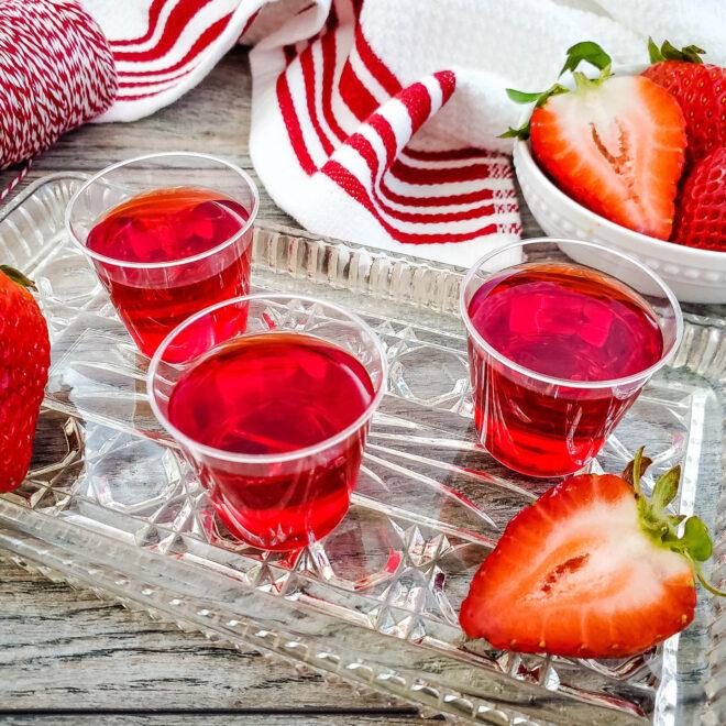 apple strawberry jello shots on a tray