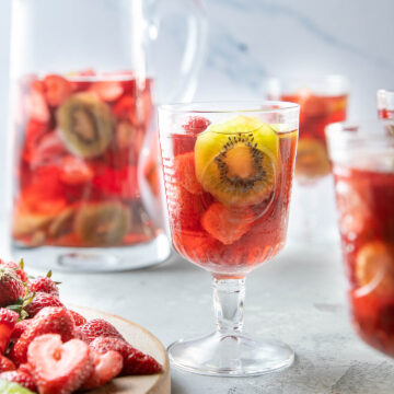 strawberry kiwi sangria in a glass with a pitcher behind