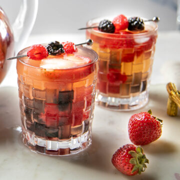 two glasses filled with triple berry sangria and fresh berries