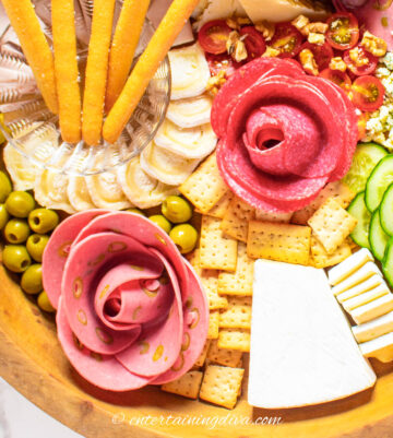 Charcuterie board with sliced meat shaped like roses