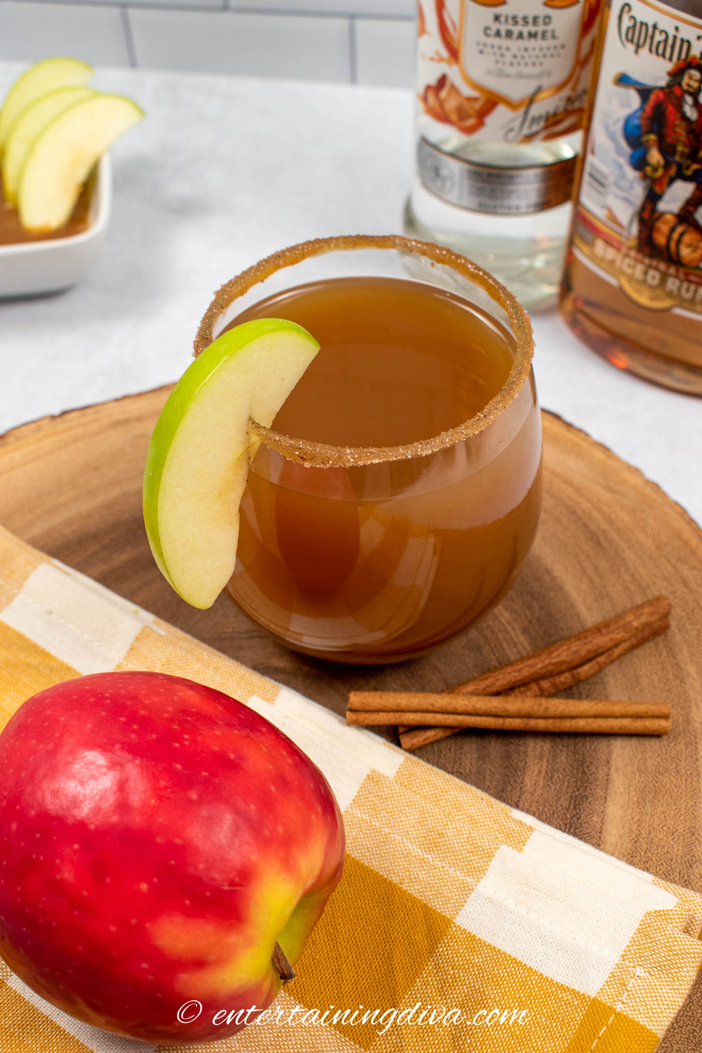 spiked caramel apple cider in a glass garnished with an apple slice