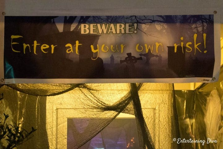 An orange porch light behind a Halloween banner adds a spooky effect