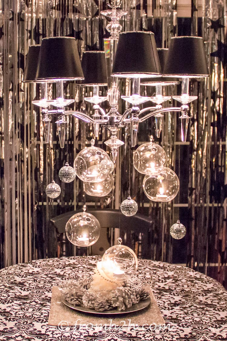 Tealights and mirror balls hanging from the chandelier are a centerpiece that doesn't take up any table space