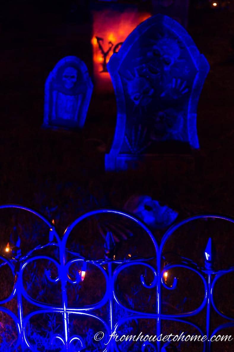 Halloween fence and tombstones lit with blue Halloween outdoor lighting