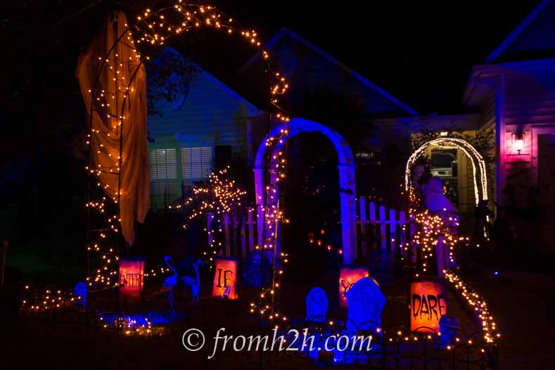 Orange and blue Halloween outdoor lighting in a front yard cemetery