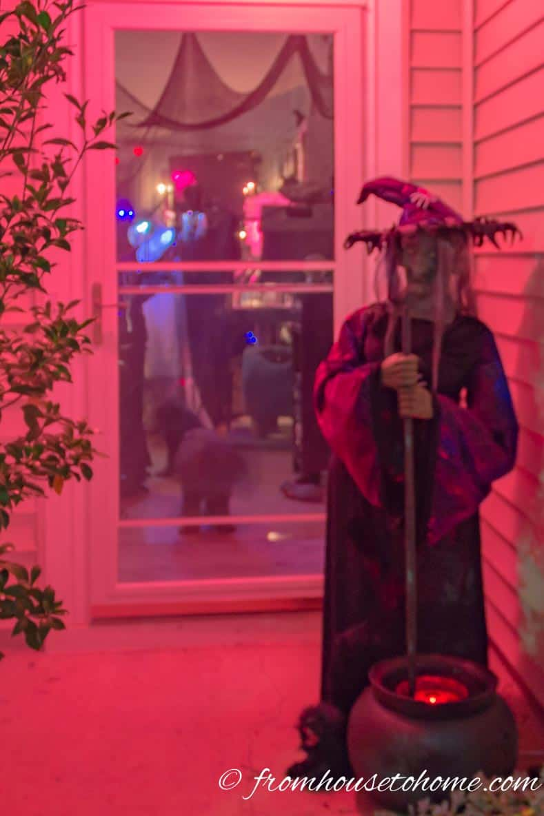 A red porch light over a Halloween witch prop