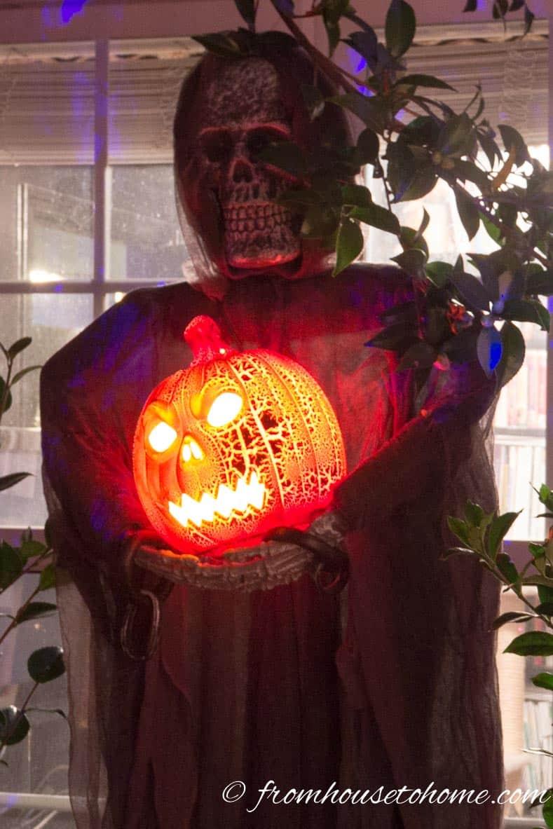Halloween outdoor pumpkin light held by a Halloween skeleton prop