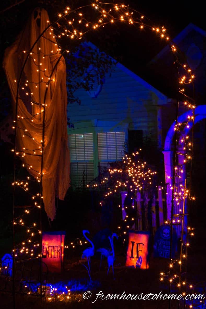 Orange String Lights Outline an arbor over a Halloween cemetery