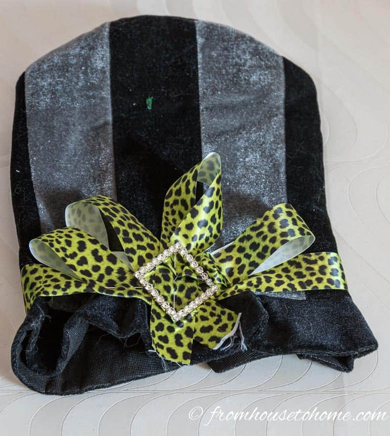 Add the sash pin or broach in the center of the bow