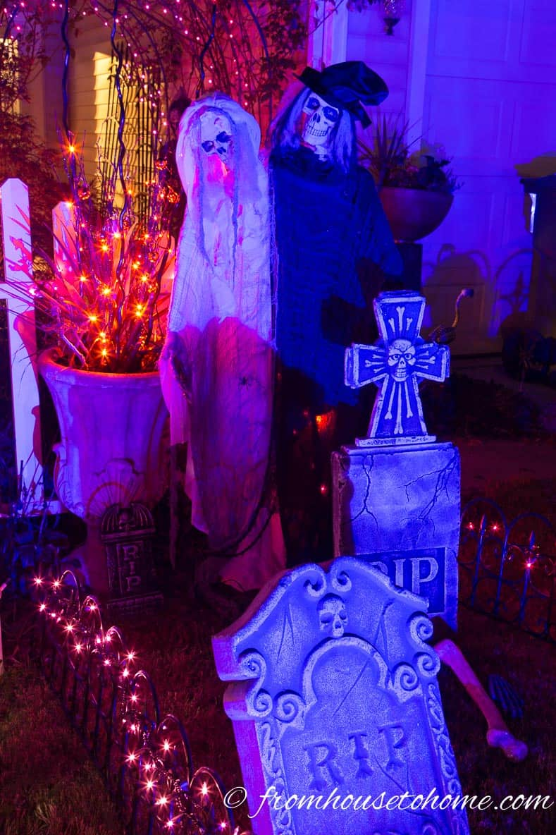 Halloween ghosts and gravestones in a Halloween graveyard lit with a blue spotlight