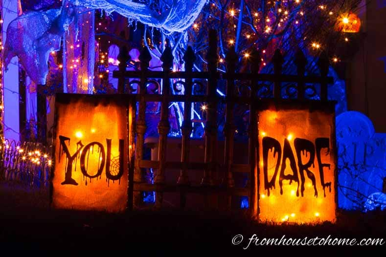 Blue and orange Halloween outdoor decor with a fence outlined with back lighting