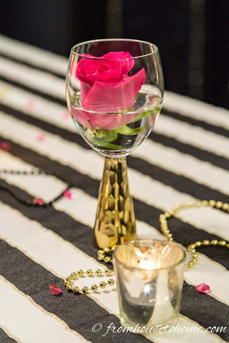 A pink rose in a gold stemmed wine glass | Kate Spade Inspired Table Setting