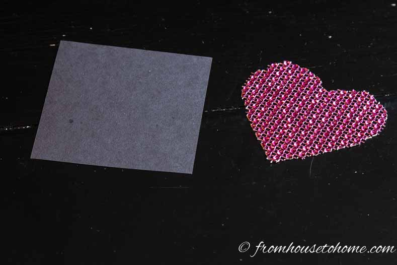 Cut a heart from the ribbon and a square from the construction paper | Easy and Free Valentines Day Table Decor Folded Napkin Envelope | I don't usually do a lot of decorating for Valentine's Day but I do like to do something elegant for the table. These folded napkin envelopes with a DIY heart place card are really easy (and inexpensive!), add a bit of Valentine's Day decor to the table but aren't too much.