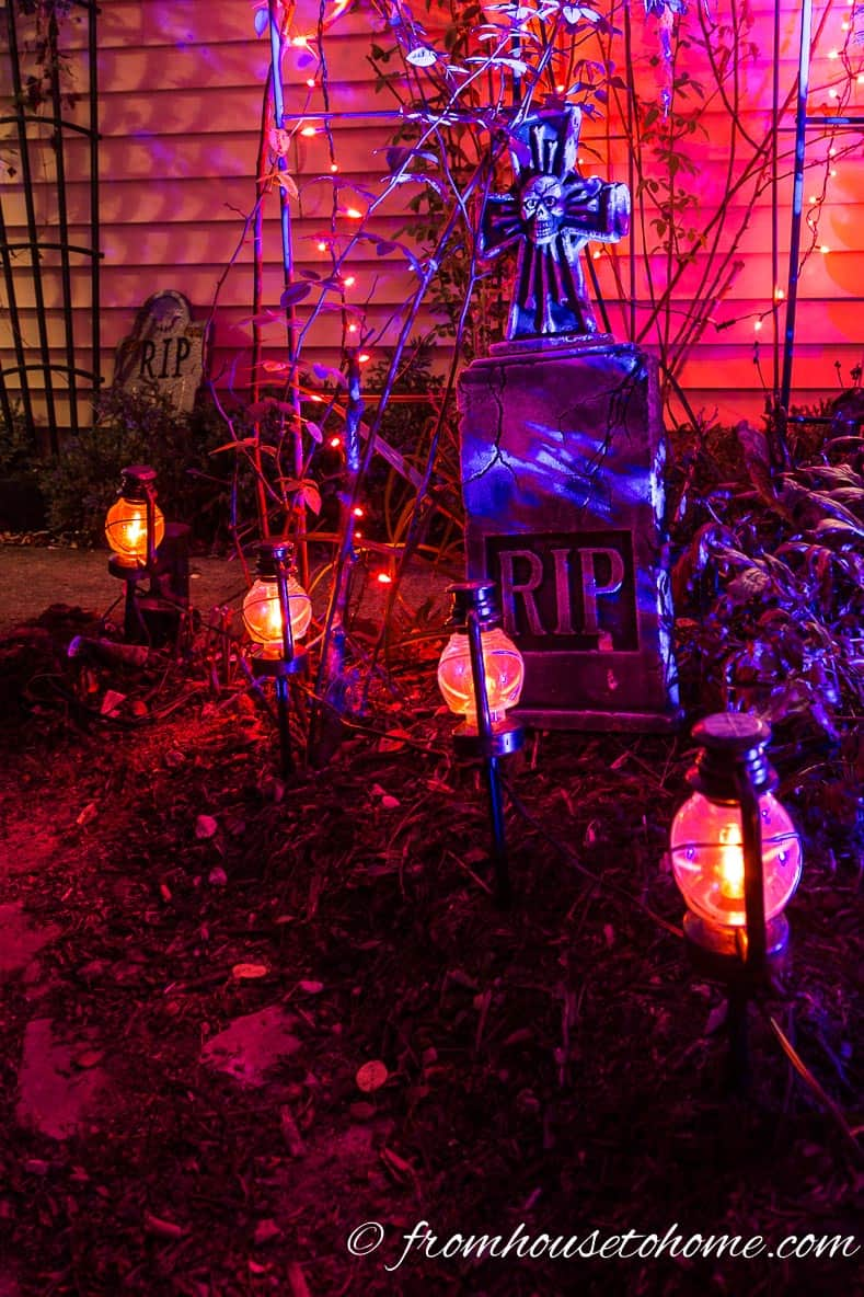 Halloween outdoor path lights in front of a tombstone
