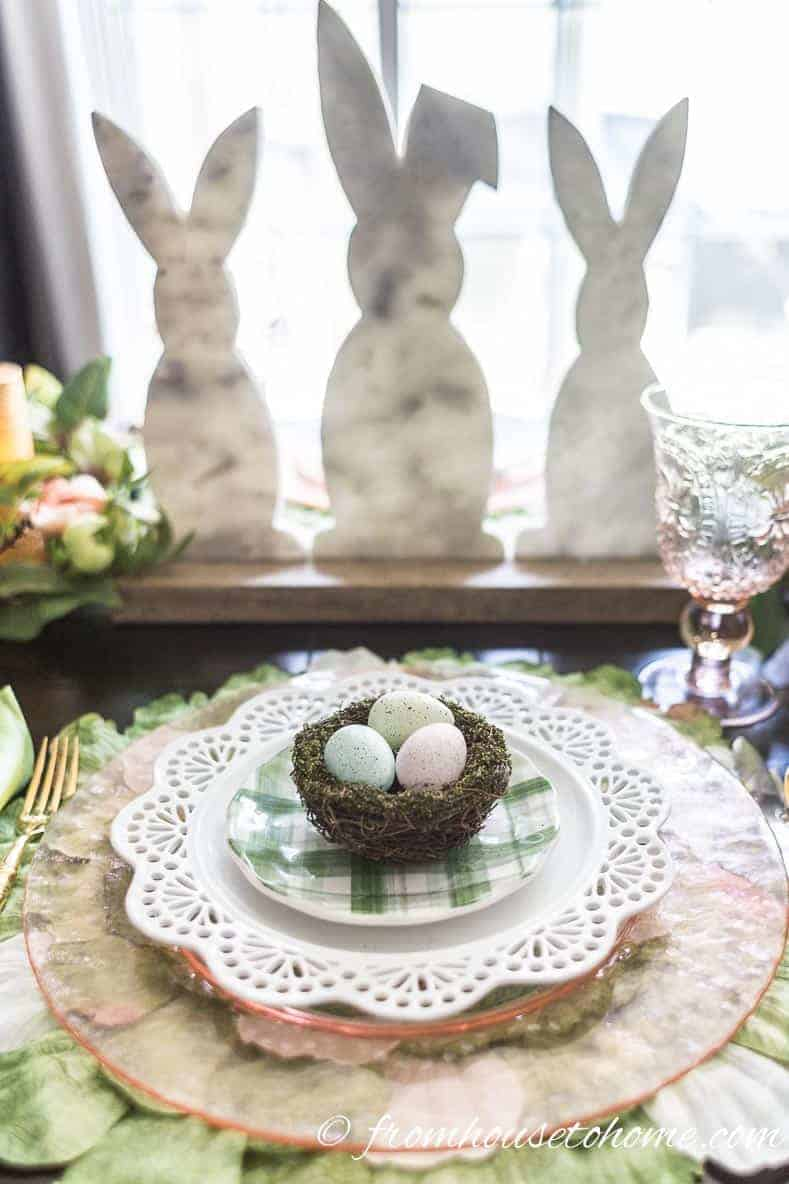Easter bunny centerpiece behind the pink and green Easter place setting