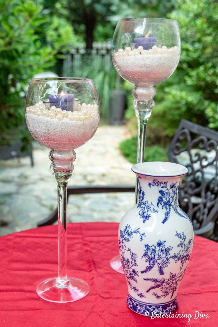 White and blue pearl and sand candles with a blue and white ginger jar on a red table cloth