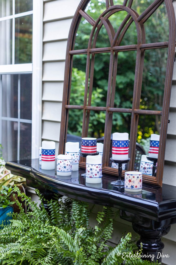 Red, white and blue candles in front of a garden mirror