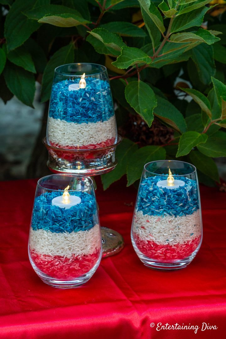 Red, white and blue rice candles on a red tablecloth for the 4th of July