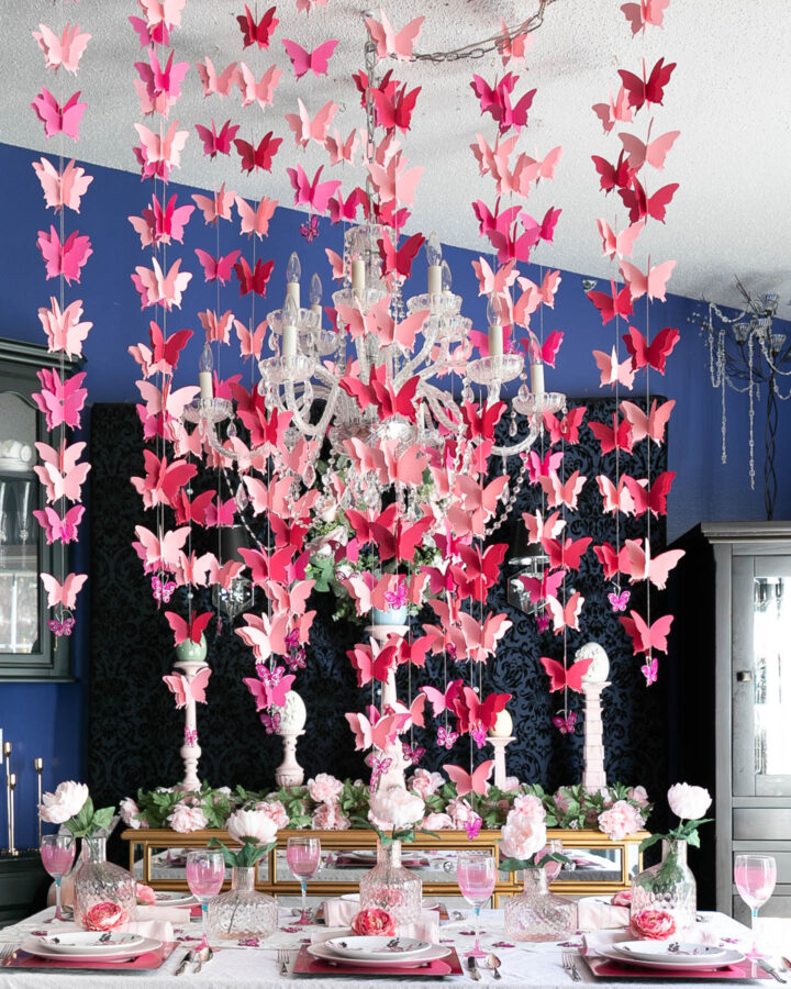 butterflies hung from the ceiling over a pink and white tablescape